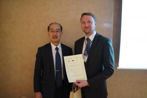 Prof. Masanori Kunieda, chairman der ISEM-XVIII Konferenz, überreicht den Excellent Paper Award an Dr. Henning Zeidler